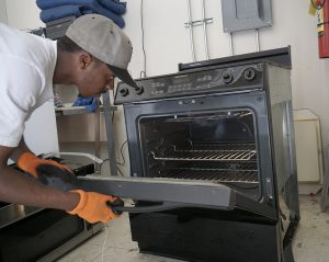 Oakland Restores assistant manager Frank Carroll tests an range/oven to make sure it works.